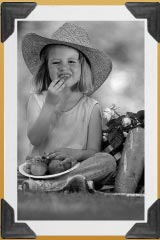 old fashioned photo of a little girl eating food from a picnic basket
